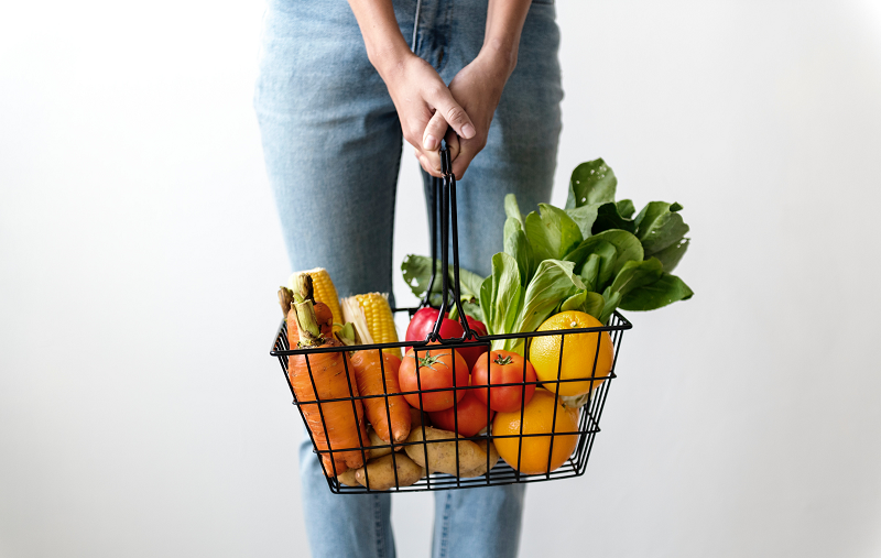 A photo of a woman holding a basket of groceries - mostly vegetables